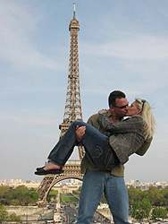 Paul holding Karla in his arms in front of the Eiffel Tower in Paris where he proposed and asked her to marry him.