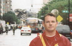 Paul in front of Building # 7 at the World Trade Center shortly after it was �pulled� by demolition with the approval of Larry Silverstein, the owner of the WTC complex